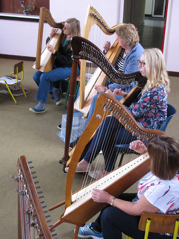 Participants practicising the Irish harp at Oideas Gael.